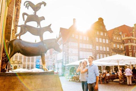 Eine Frau und ein Mann stehen vor den Bremer Stadtmusikanten. Die Frau macht von der Bronzestatue ein Bild.