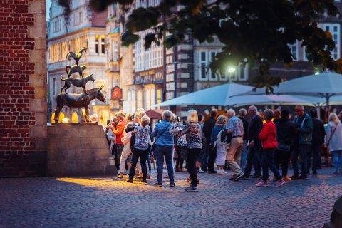 Die Aufnahme zeigt viele Menschen, die am Abend vor der Bronzestatue der Bremer Stadtmusikanten stehen und Bilder machen.
