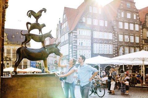 Eine Frau und ein Mann stehen vor den Bremer Stadtmusikanten. Die Frau fasst an den Mund des Esels und lächelt dabei. Der Mann steht hinter ihr und beobachtet die Statue.