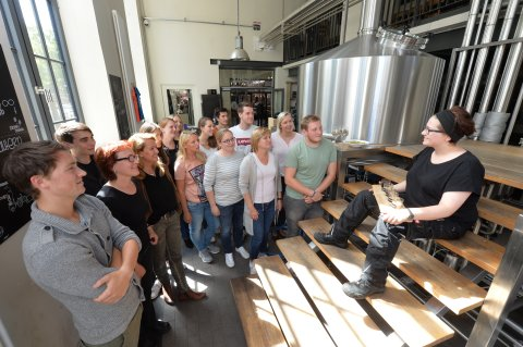 Eine Mitarbeiterin der Union Brauerei führt eine Brauereiführung für Gäste durch.
