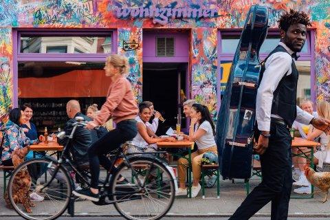 Ein junger Mann mit Weste, Fliege und einem Cello-Koffer, passiert die Kneipe Wohnzimmer im Bremer Viertel, vor der zahlreiche Menschen unterschiedlichen Alters auf Bierbänken Getränke und die Gesellschaft genießen.