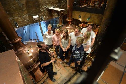 Teilnehmende einer Brauereiführung hören dem Braumeister im Schüttinger zu