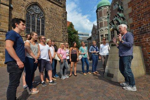 Ein Gästeführer erzählt einer jungen Gruppe bei einer Stadtführung an den Bremer Stadtmusikanten Wissenswertes über Bremen
