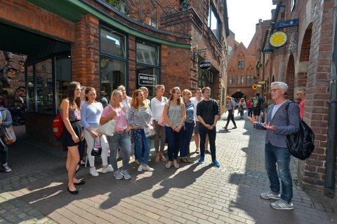 Ein Gästeführer erzählt einer jungen Gruppe bei einer Stadtführung in der Böttcherstraße Wissenswertes über Bremen