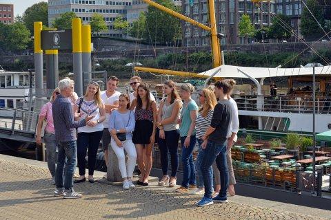 Ein Gästeführer erzählt einer jungen Gruppe an der Schlachte Wissenswertes über Bremen