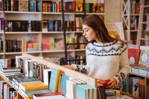 Eine junge Frau steht in einer Buchhandlung vor einem tischhohen Regal und schaut sich die Bücher an. Im Hintergrund stehen große Bücherregale.