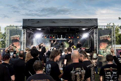 Metal Fans stehen vor einer Bühne und feiern.