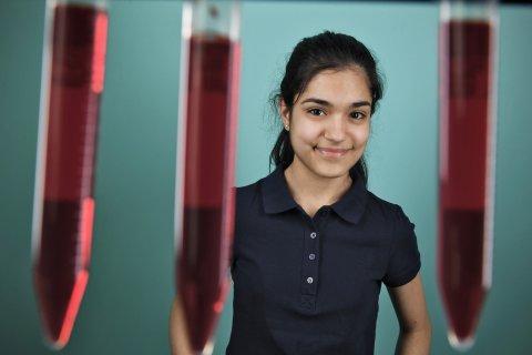 Ein Mädchen vor türkisem Hintergrund und hinter drei roten Reagenzgläsern