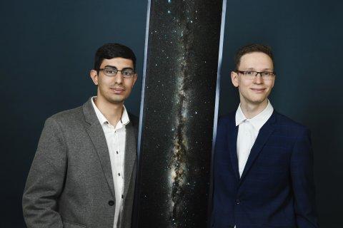 Zwei Jugendliche im Anzug vor dunklem Hintergrund und einem Bild der Milchstraße