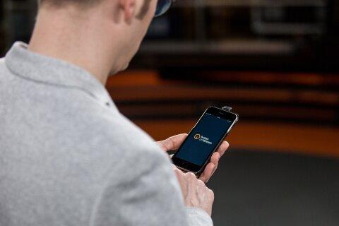 Der buten un binnen-Moderator Felix Krömer wurde über die Schulter fotografiert, während er sein Smartphone in der Hand hält und die buten un binnen-App aufruft..