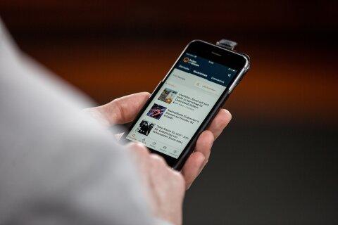 Der buten un binnen-Moderator Felix Krömer wurde über die Schulter fotografiert, während er sein Smartphone in der Hand hält und die buten un binnen-App benutzt.