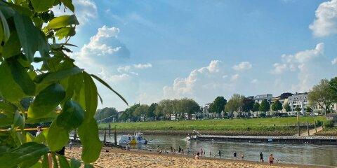 Ausblick auf den Strand am Café Sand, auf der Weser die Sielwallfähre und ein Binnenschiff, am Strand Menschen in Badekleidung, am linken Bildrand grüne Blätter eines Baumes