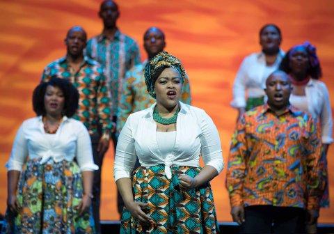 Eine Solistin trägt ein afrikanisches Gewand und steht singend auf einer Bühne. Im Hintergrund ein Teil des Chors.