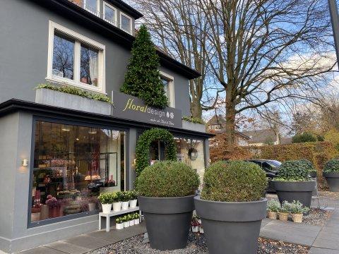 Der Laden von außen. Davor stehen runde Büsche und ein Tannenbaum auf dem Dach.