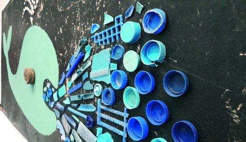 Ein Walbild aus Flaschendeckeln in der Wallerie von Chris Landrock.