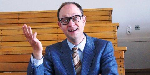 Christian Schliehe sitzt im Anzug und hebt die Hand fragend in die Luft, während er lächelt.
