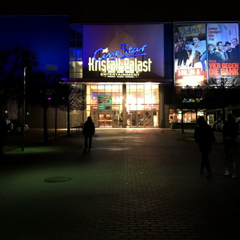 Die beleuchtete Frontseite des Cinestar in der Dunkelheit.