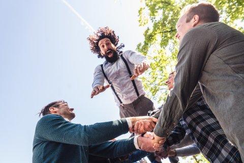 Eine Gruppe von Männern hält die Arme verschränkt. Ein anderer springt in die Arme hinein.