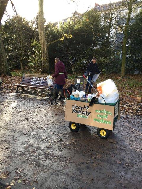 Zwei Menschen sammeln Müll in Bremen auf. Vorne an steht ein Bollerwagen mit der Aufschrift: clean up your City Bremen. Machen, nicht meckern.