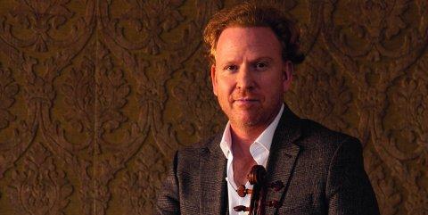 Der Musiker trägt einen braunen Anzug und sitzt auf einem Tisch. In seiner linken Hand hält er seine Violine