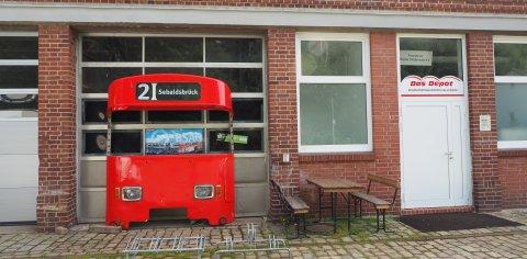 Der Eingangsbereich vom Straßenbahnmuseum in Sebaldsbrück. Zu sehen ist die Eingangstür mit Sitzgelegenheiten und der Front einer roten Straßenbahn