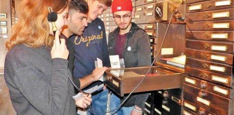 Vier Jugendliche lesen und hören Informationen in einer Schublade