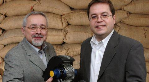 Zwei Männer halten eine Kaffeemaschine