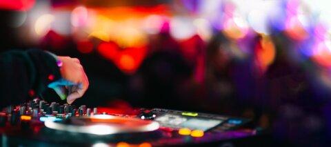 DJ Pult und im Hintergrund befinden sich unscharf tanzende Menschen.