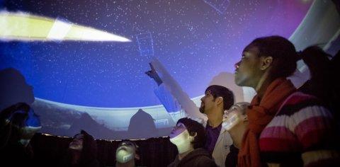 Ein Mann zeigt einer Gruppe von Schülern etwas an einer Wand.