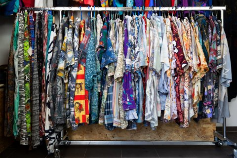Eine Auswahl an bunten Hemden hängt an einer Kleiderstange.