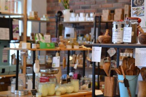 Zu sehen ist das Sortiment des Ladens. Es befindet sich im Vordergrund Holzgeschirr und im Hintergrund sind Hygieneprodukte zu sehen.