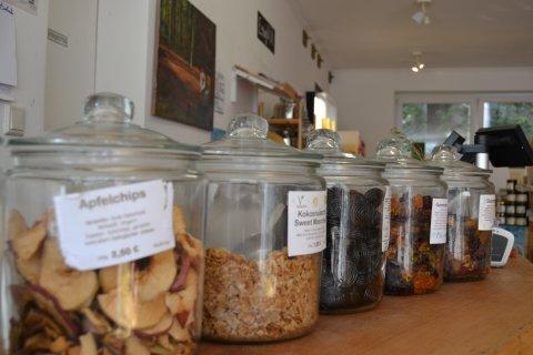 Zu sehen sind diverse Aufbewahrungsboxen aus Glas mit verschieden Süßigkeiten, wie Apfelchips, Lakritzstangen und Gummibärchen.