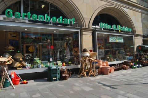 Das Geschäft von außen. Es stehen verschiedene Blumentöpfe und Vogelhäuser vor dem Laden.