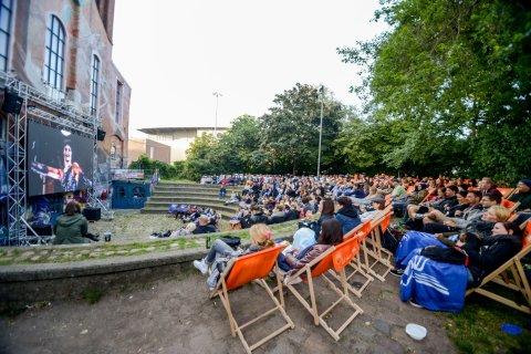 Mehrere Menschen sitzen auf Stühlen im Freien und schauen sich einen Film an.