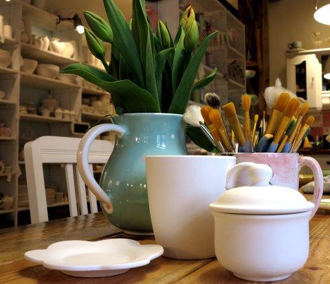 Mehrere Keramikgefässe, die auf einem Holztisch stehen. In eine Keramiktasse wurden Pinsel gesteckt, in einer weiteren grüne Pflanzen.Im Hintergrund sind Regale mit weiteren Keramikprodukten zu sehen.