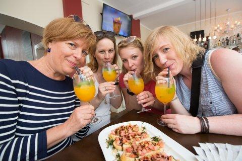 Vier Frauen trinken einen Cocktail und haben Häppchen vor sich stehen.