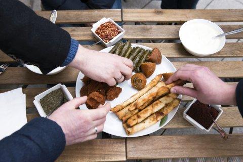 In der Mitte des Bildes steht ein Teller auf einem Holztisch. Auf dem Teller liegen kulinarische Kostproben, beispielsweise Falafel. Drei Hände greifen nach dem Essen auf dem Teller.