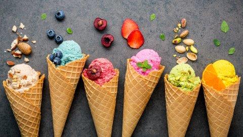 Zu sehen sind verschiedene Eissorten wie Nuss, Blaubeere, Kirsche, Erbeere, Pistazie und Orange. Die Eiskugeln befinden sich in Waffeln.