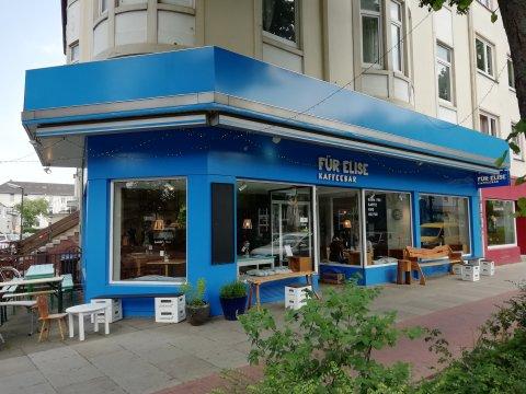 Das Café von außen mit blauer Außenfassade und Sitzgelegenheiten.