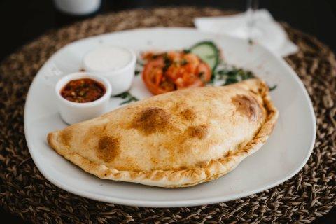 Tellergericht mit einer Empanada, dazu Saucen und Salatbeilage.