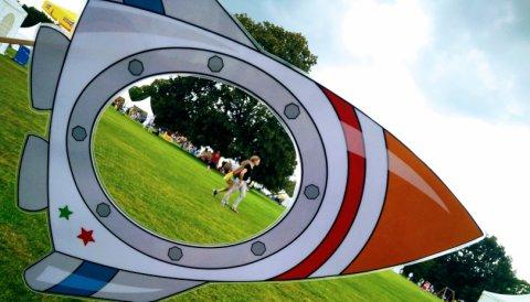Eine Papprakete mit einem Guckloch in einem Park. Durch das Guckloch sieht man Menshen vorbeilaufen und weiße Zelte stehen.