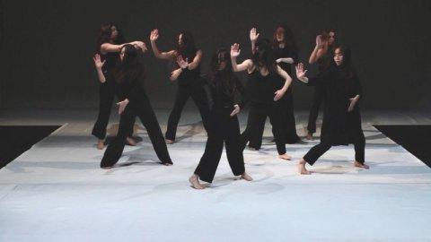 In schwarz gekleidete Menschen tanzen auf einer Bühne