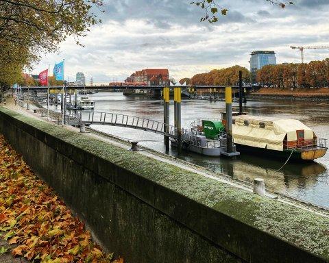 Blick auf die Weser. Es liegen herbstliche Blätter auf dem Boden und ein Schiff liegt am Anleger.