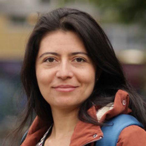 Das Portrait einer Frau mittleren Alters mit dunklen Haaren, die in die Kamera schaut.