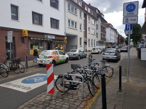 Ein Piktogramm auf dem Straßenbelag und die Beschilderung am Straßenrand weisen die Straße als Fahrradstraße und Teil einer Fahrradzone aus