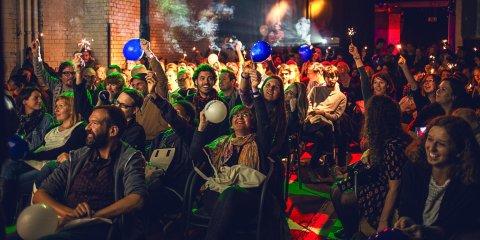 Besucher des Favourites Film Festival halten Luftballons und Wunderkerzen in die Luft.