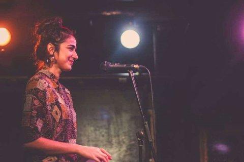 eine Frau steht auf einer Bühne und lächelt.