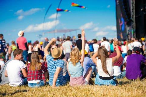 Festivalbesucher sitzen auf einer Wiese vor einer Festivalbühne