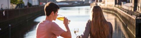 Ein Pärchen sitzt in der Abendsonne auf der Terrasse der Feuerwache in der Überseestadt und blickt auf das Hafenbecken.