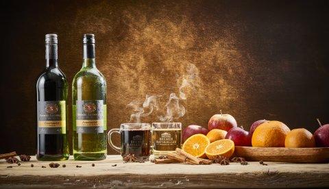 Je eine Flasche und je ein Glas mit weißem und rotem Glühwein auf einem Tisch mit Äpfeln, Orangen, Zimt, Anis und Nelken